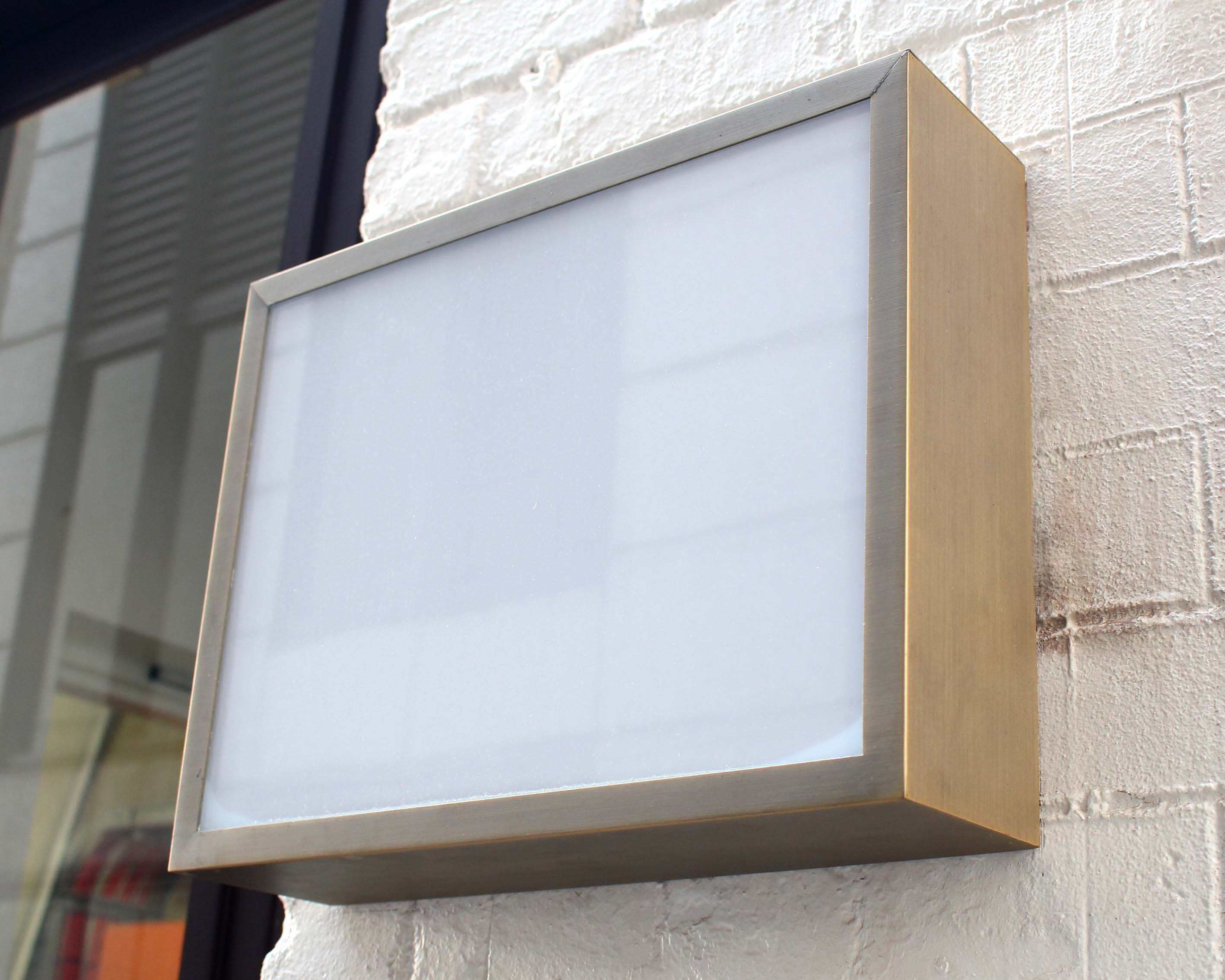An external signage illuminated lightbox with a stainless steel frame attached to a wall.