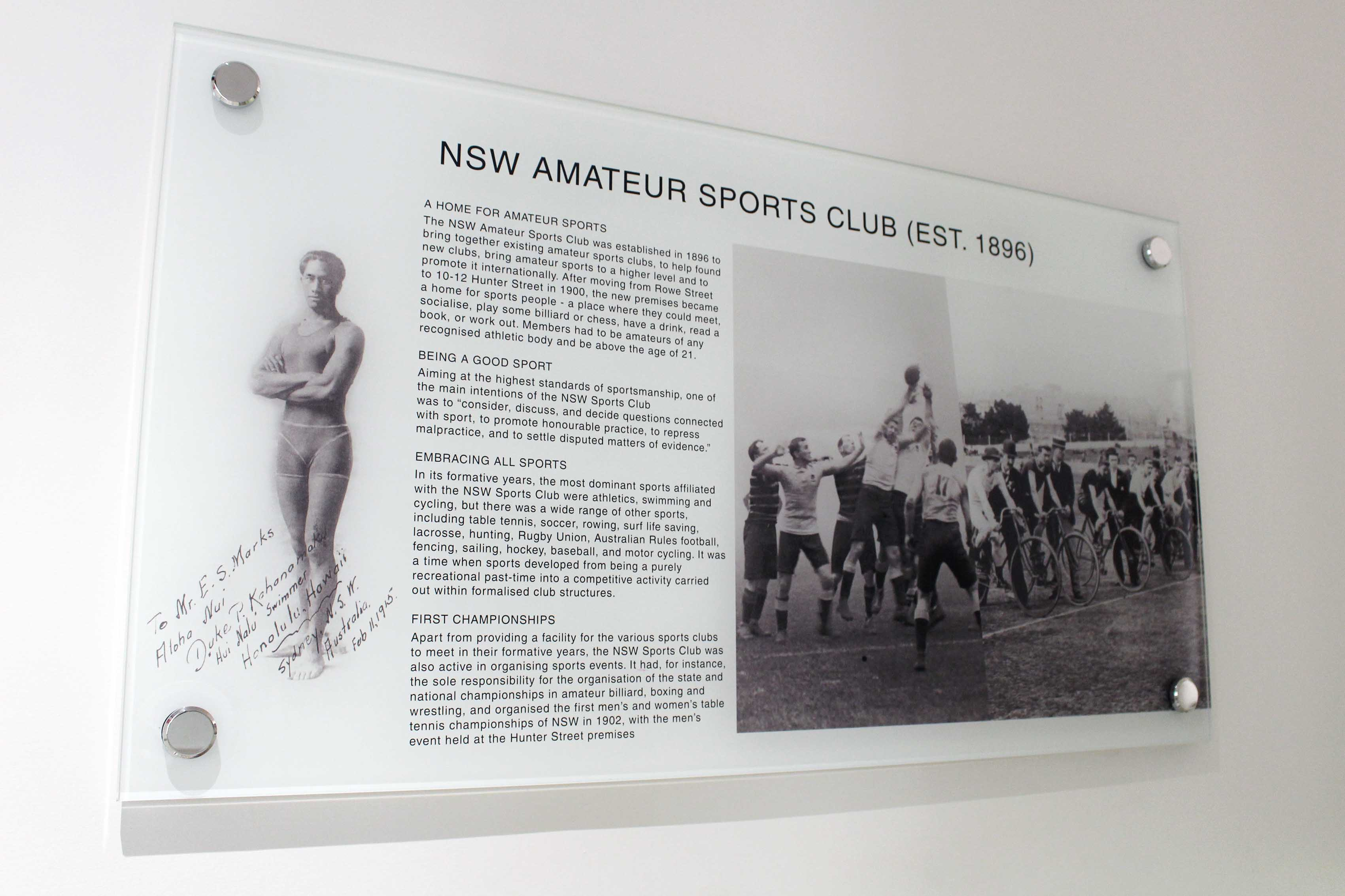 Pin mounted glass informational and pictorial black and white display of the NSW Amateur Sports Club.