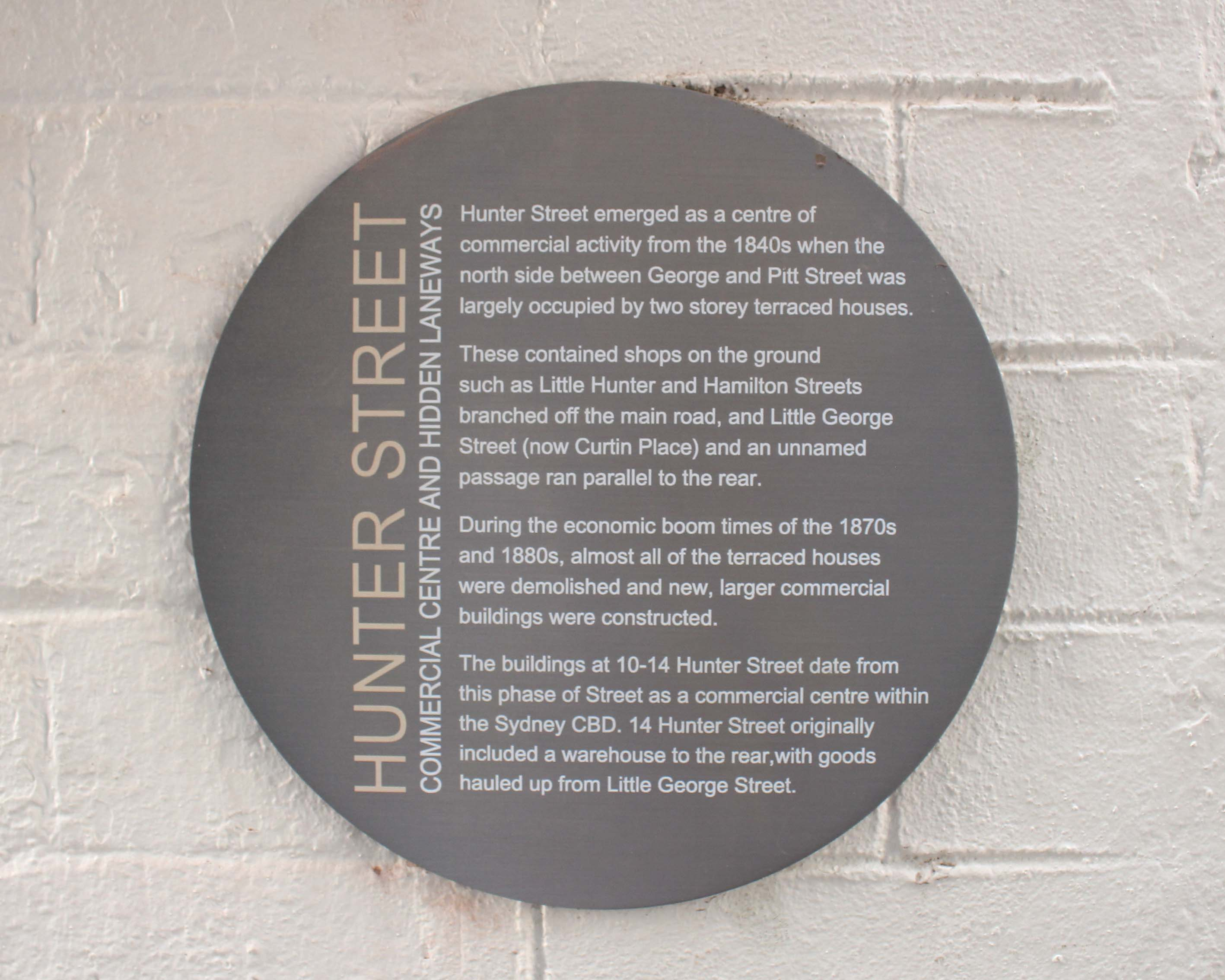 A stainless steel circular external wall plaque digitally printed showing the road map and intersection of George and Hunter Street.