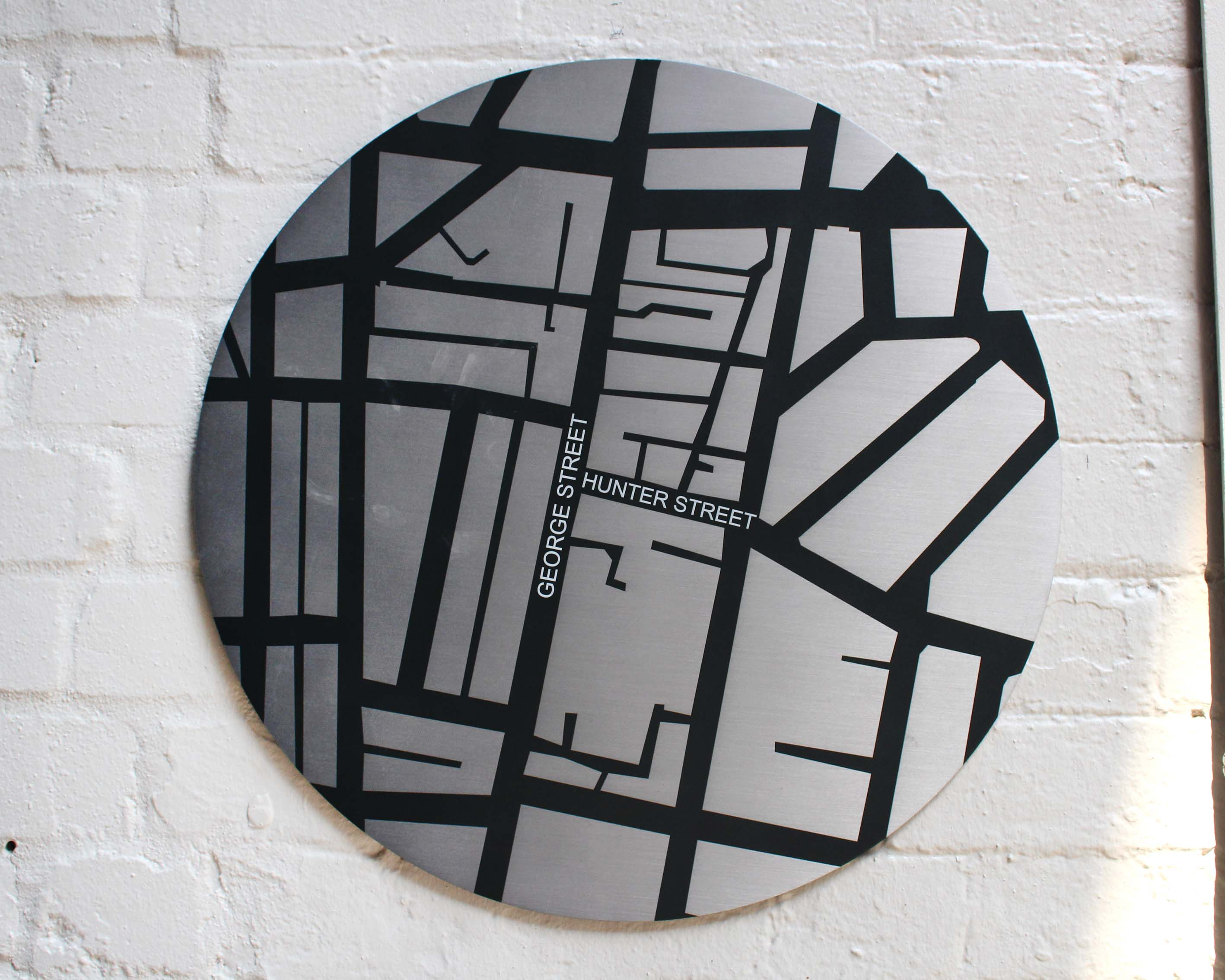 A stainless steel digitally printed external wall plaque showing the road map and intersection of George and Hunter Street.