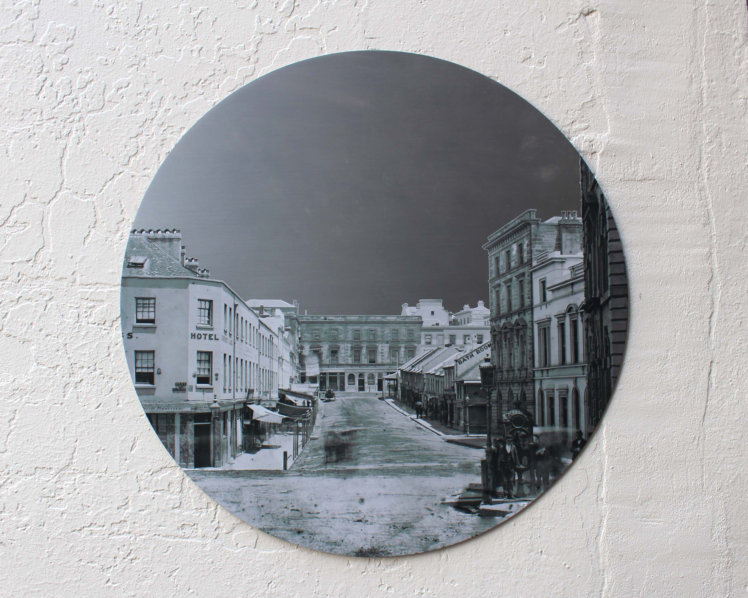 A circular stainless steel digitally printed wall plaque with a black and white historical picture of Hunter Street.