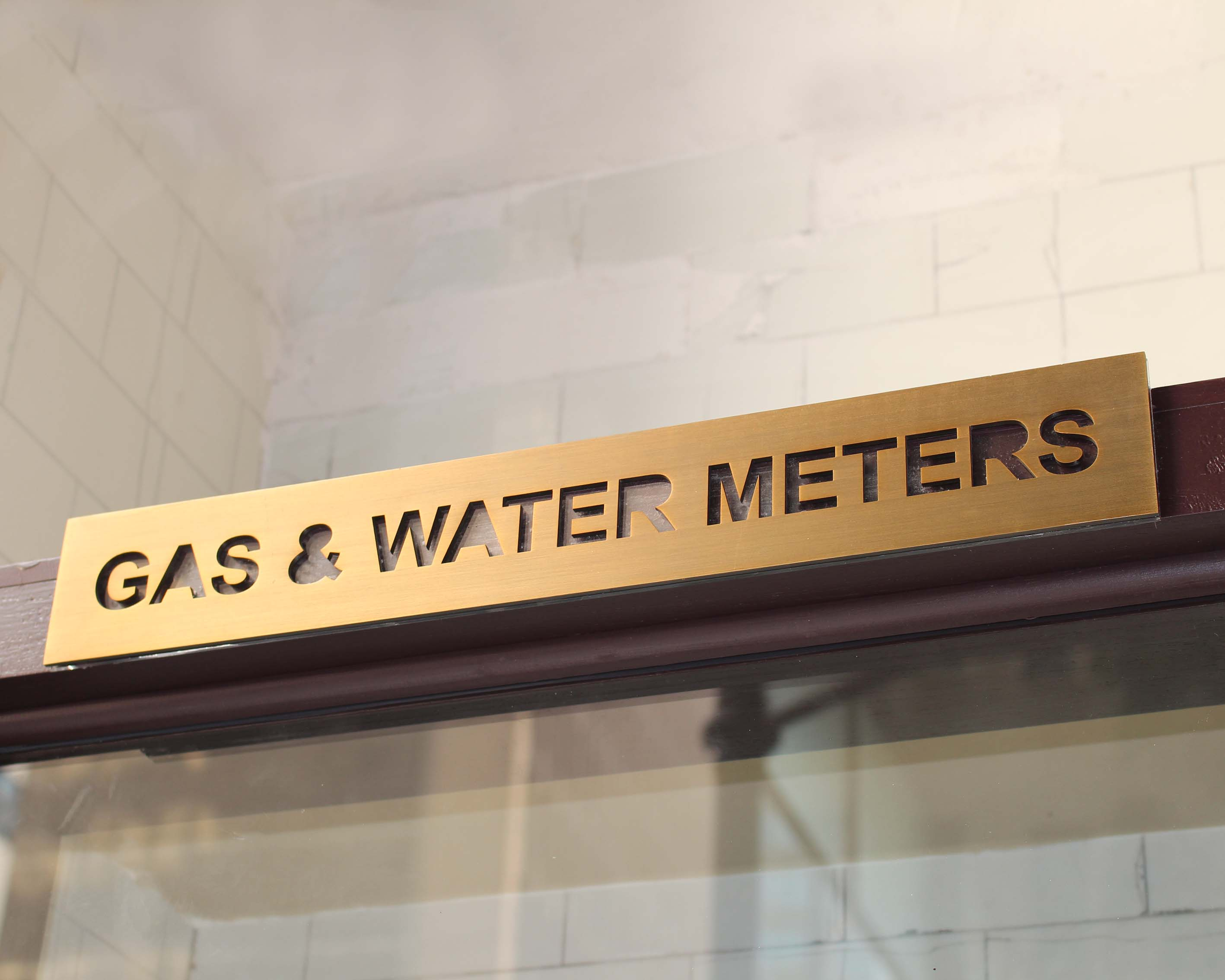A photo of a brass laser cut gas and water service sign