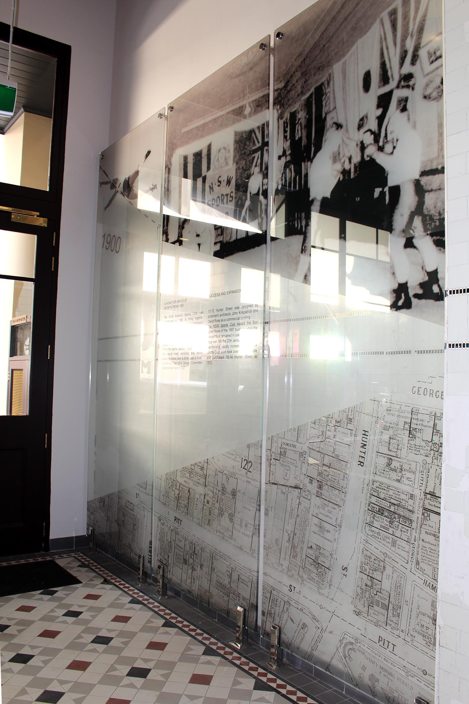 Three large pin mounted glass panels with various black and white images of the NSW Sports club in its heyday.
