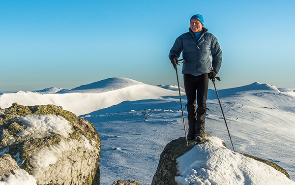 Photo of a man standing with walking poles on rock with snowy mountains behind him