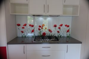 Kitchen featuring a custom printed glass splashback of red flowers.