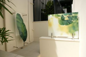 Two outdoor interpretive glass digitally printed graphic panels with garden artwork imagery