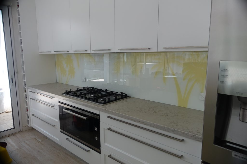 Kitchen with a custom kitchen glass splashback with palm tree imagery