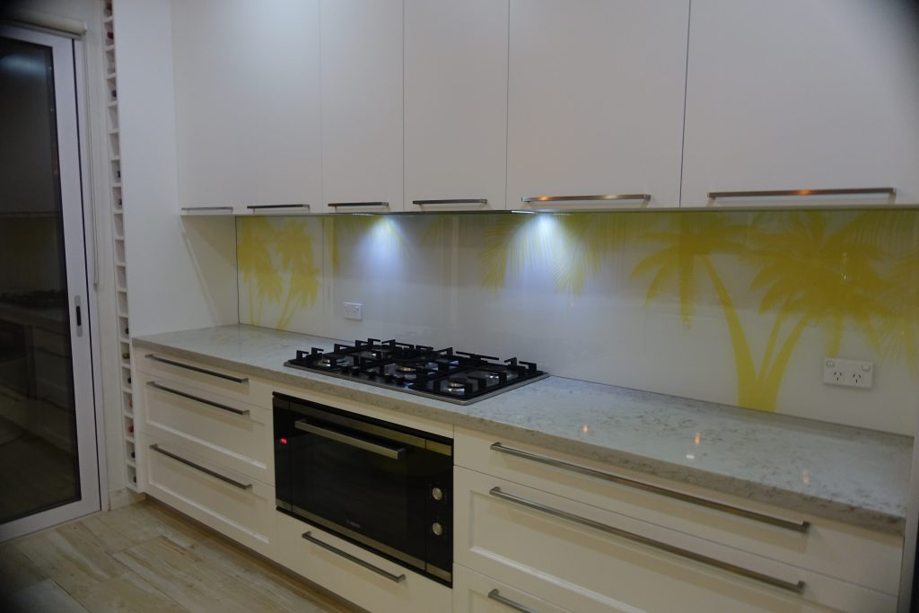 A kitchen with a custom glass printed splashback of yellow palm trees on a white background