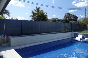 Photo of a pool in the progress of installing a glass fence