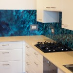 Kitchen with a custom digitally printed glass splashback of sea water and rock imagery