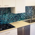 Kitchen with a custom printed glass splashback of sea water and rock imagery