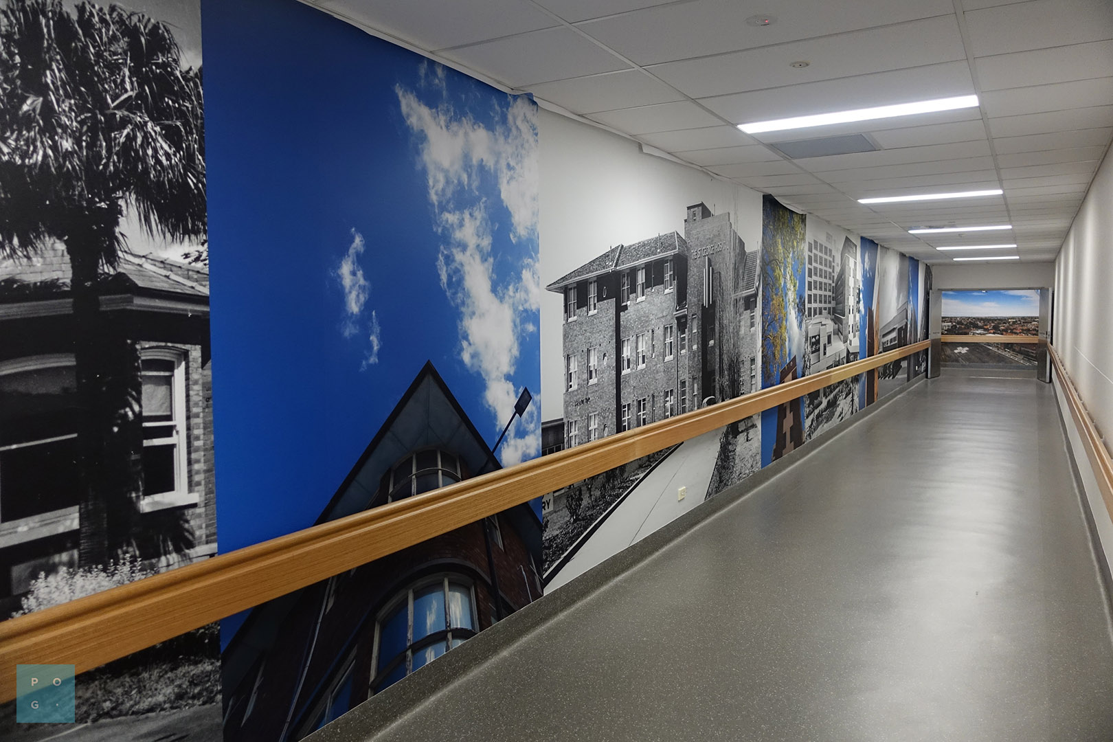 Hospital hallway with custom printed wallpaper panels with the hospital building imagery.