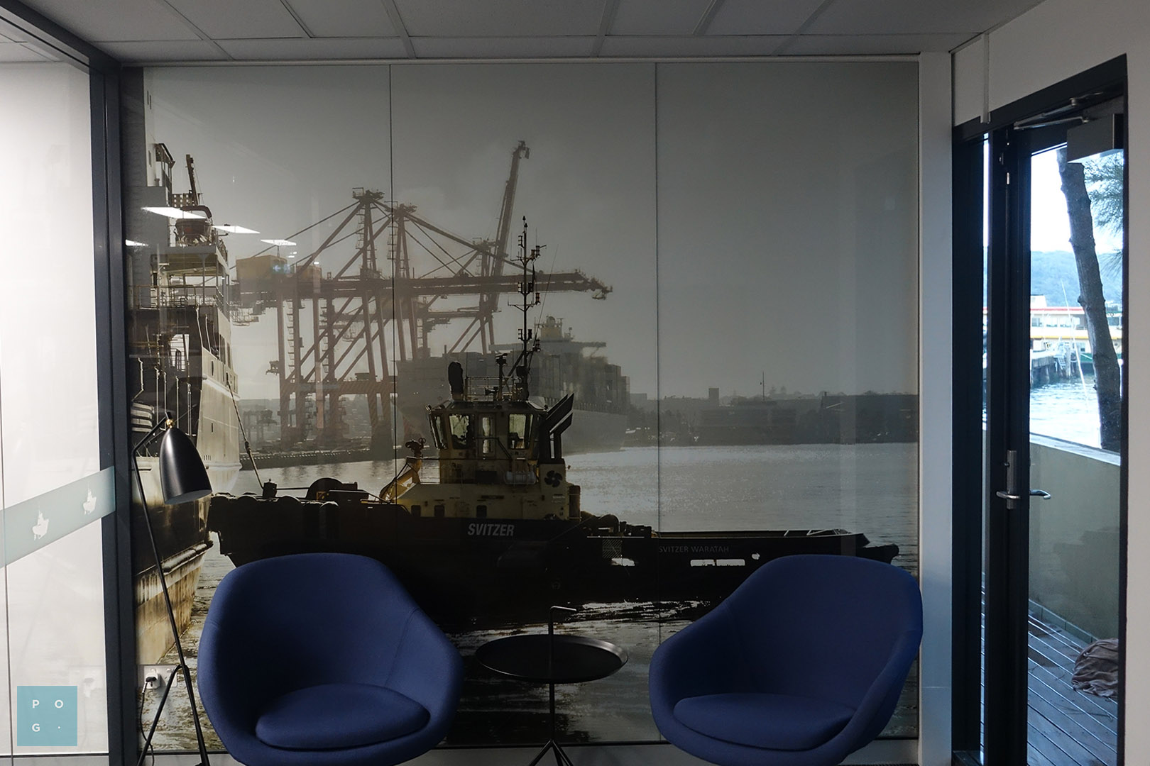 Office with a wall mounted large glass print featuring a tugboat in harbour.