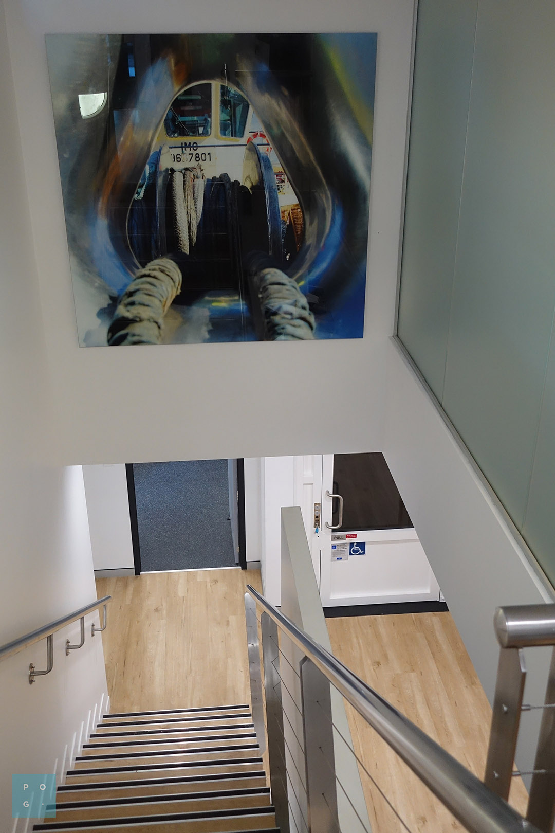 Large glass wall print of tugboat imagery on the overhead stairwell wall.