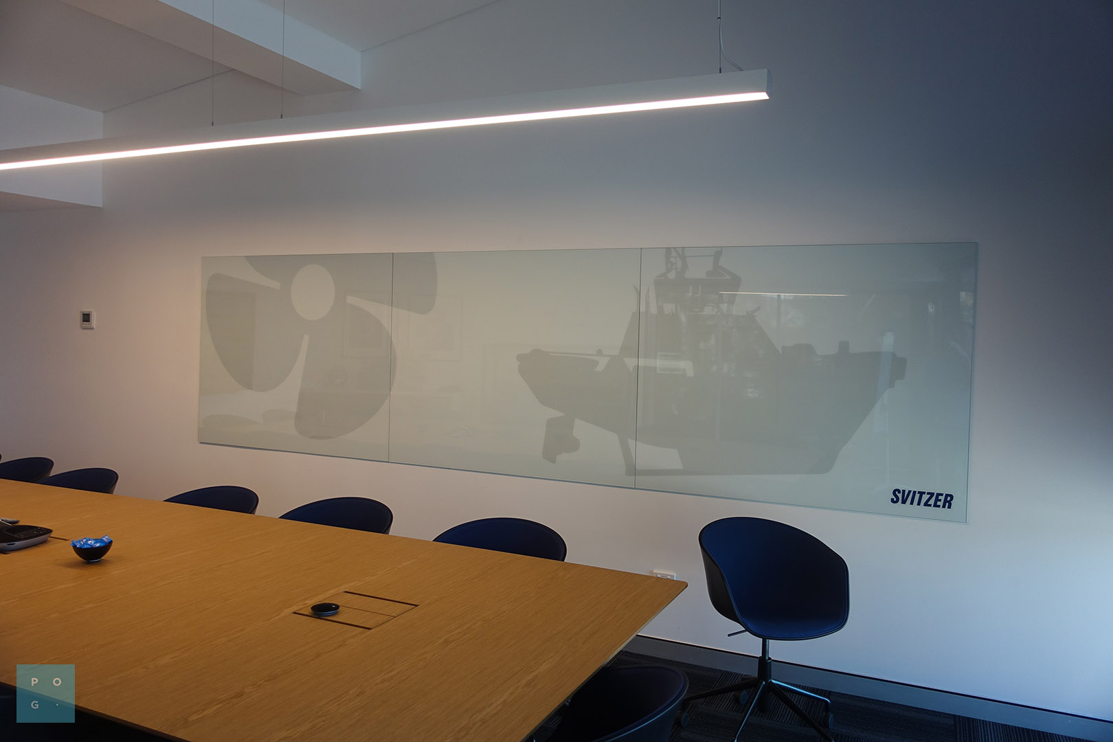Boardroom with a large, three panel glass wall print with tugboat imagery on the wall.