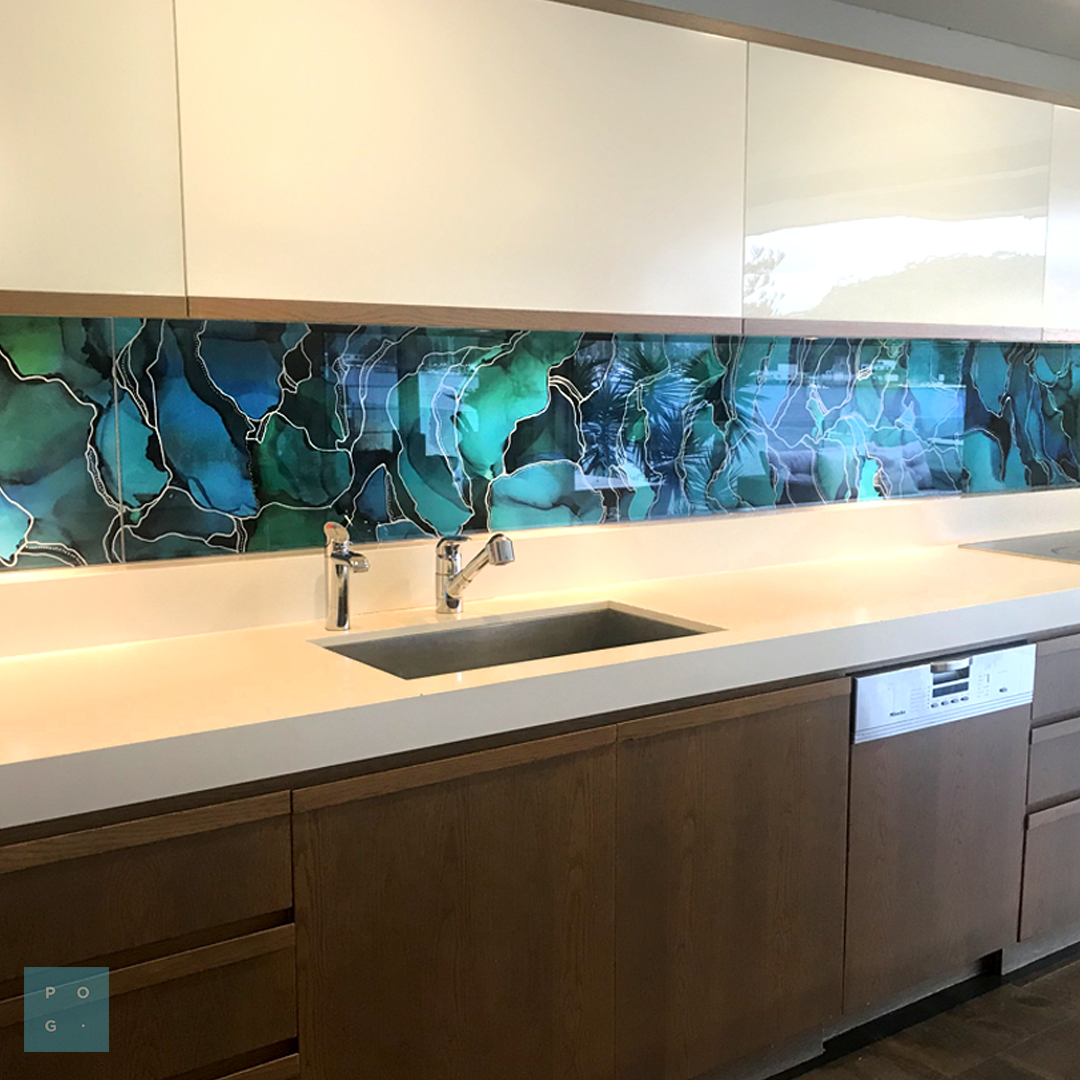 A kitchen with a custom printed green and blue glass splashback.