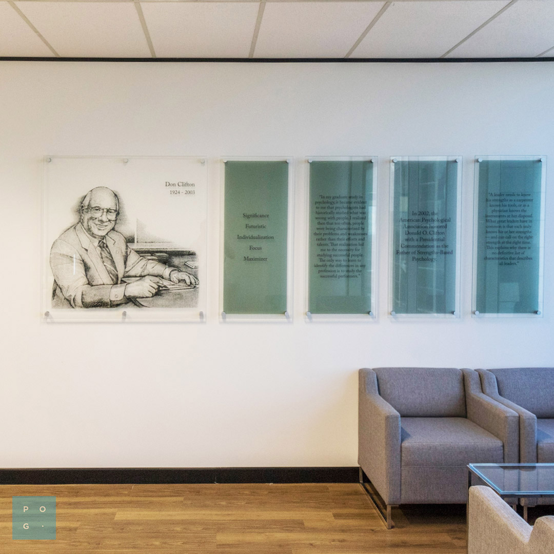A large pin mounted glass print of Dan Clifton alongside four more frosted glass panels with descriptive text.